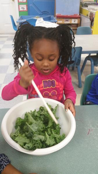 Stirring kale and dressing for a winter salad.