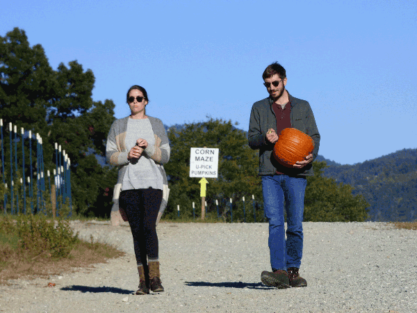 A woman and a man carrying a pumpkin at an agritourism farm