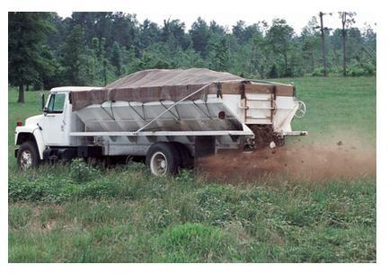 Photo of spreader truck discharging litter onto field