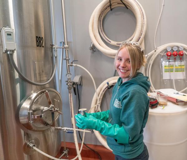Photo of brewer checking fermentation tank lines