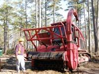 Red-metal bull dozier sized biomass harvester roughly tank-size