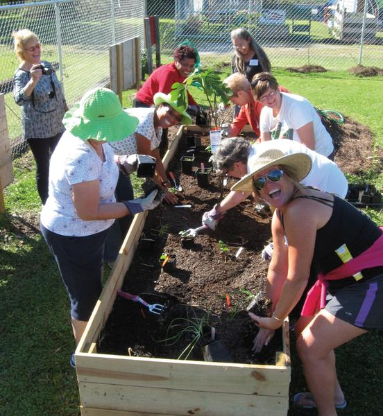 A photo of volunteers preparing a raised-bed planter.