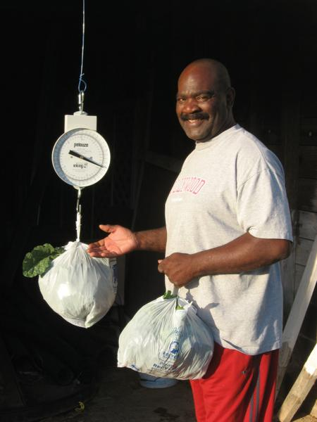 A man weighs bags of produce.