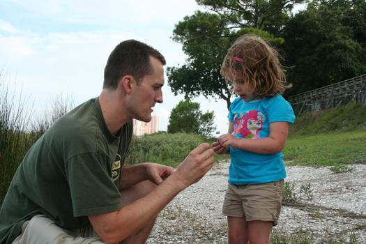 An adult and a young girl examine a small object outdoors