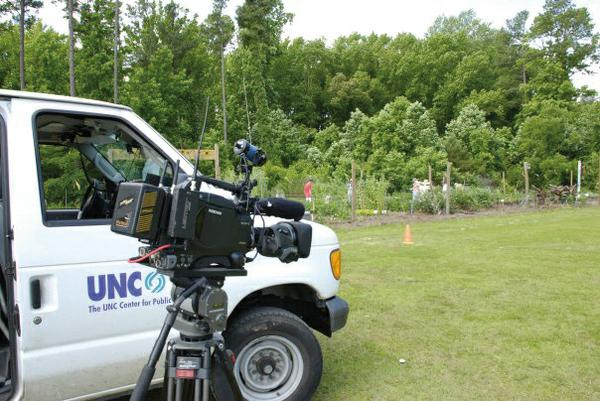 Photo of a news station videotaping at a community garden.