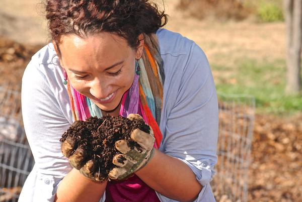 Photo of smiling woman holding a handful of compost