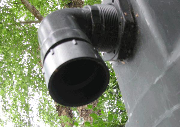 Underside view of an open downspout from a tank