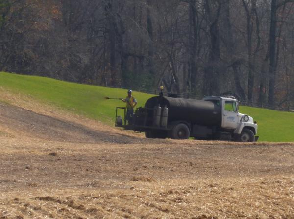 Figure 1. Asphalt is being applied to straw as a tackifier. Note
