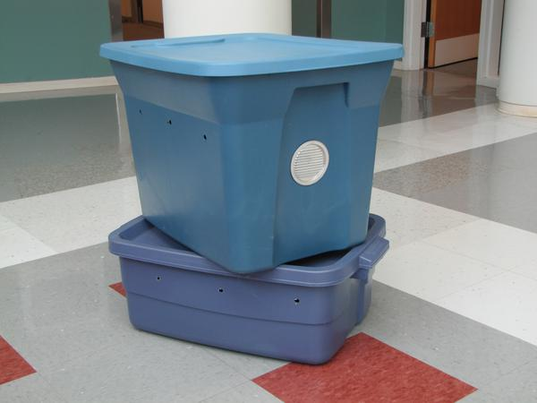 Figure 1. Plastic storage bins in a dark color with tight-fittin