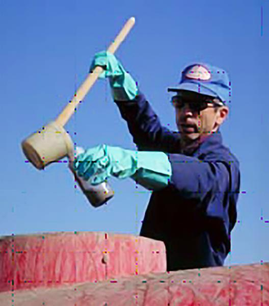 Photo of person dipping a sludge sample from top of tanker