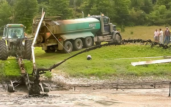 Photo of sludge being pumped from the lagoon into a tanker