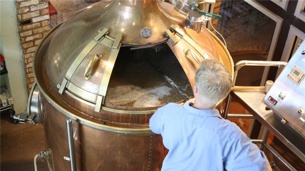 Photo of distillery employee stirring mash in a copper container