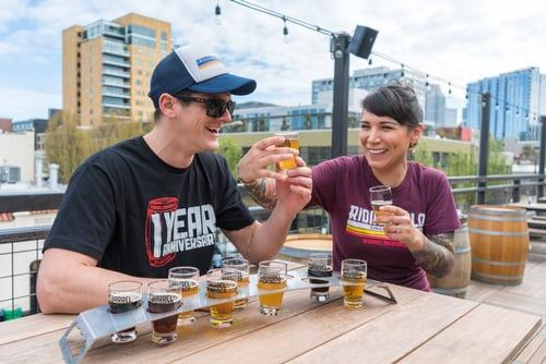 Two festival-goers sitting at table sampling beer flights