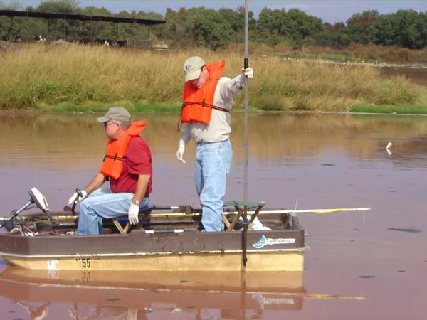 Photo of two people in life vests sampling in small boat