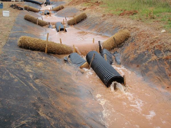Solid blocks of PAM in corrugated pipes in a swale.