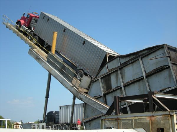 Truck on a hydraulic lift tiled at 45% or more to empty chips.