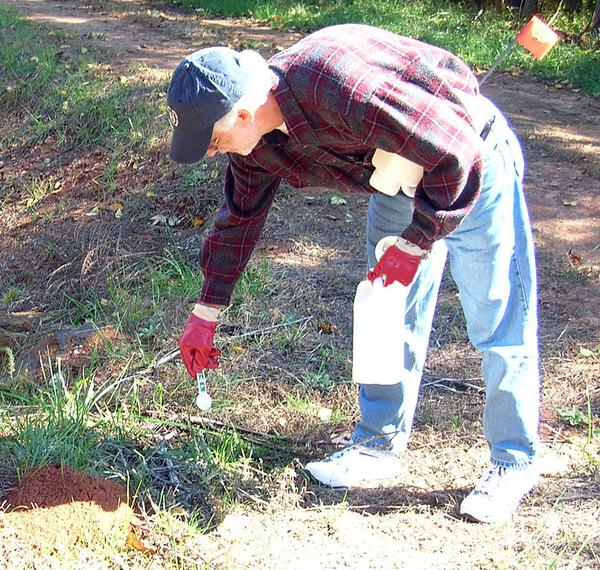 Applying a granular fire ant bait around a mound