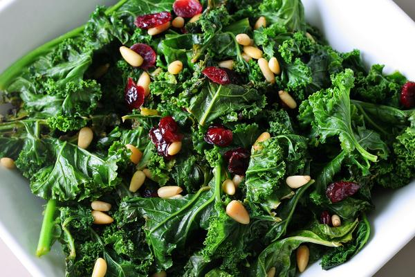 Photo of kale with pine nuts and cranberries in a bowl.