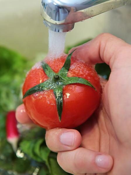 Photo of a tomato being washed under a faucet.