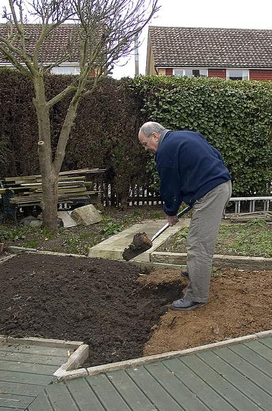 Photo of a man digging in an urban garden.