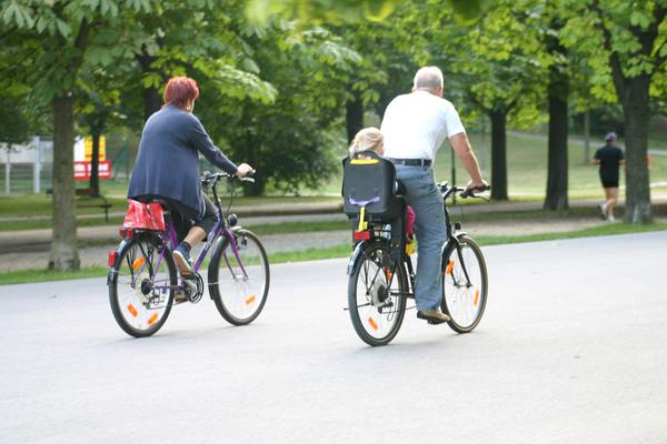 Picture of a man and a woman riding bicycles in a park