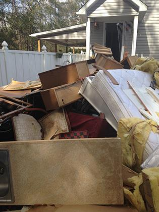 Furniture piled in front of house after flood
