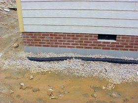 A foundation drain being installed around a new home