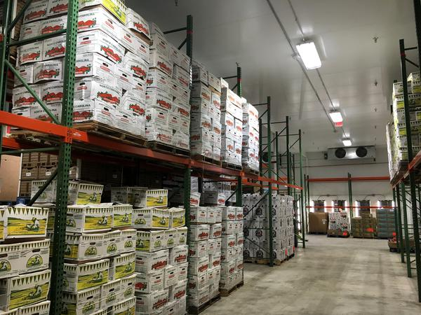 A food bank warehouse with boxes of produce.