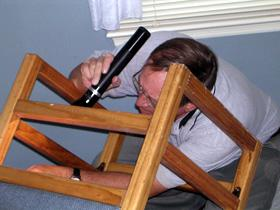 Inspecting the underside of a chair for signs of bed bugs