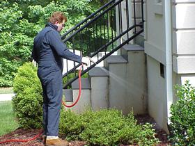 A pest control technician treating the exterior of a house